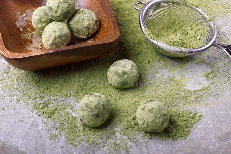 Ball sweets covered with matcha tea powder on a parchment paper stock photo