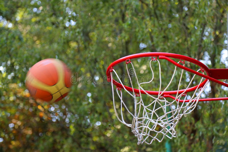 The ball thrown at basketball hoop. Throw the ball to the basketball hoop red royalty free stock photo