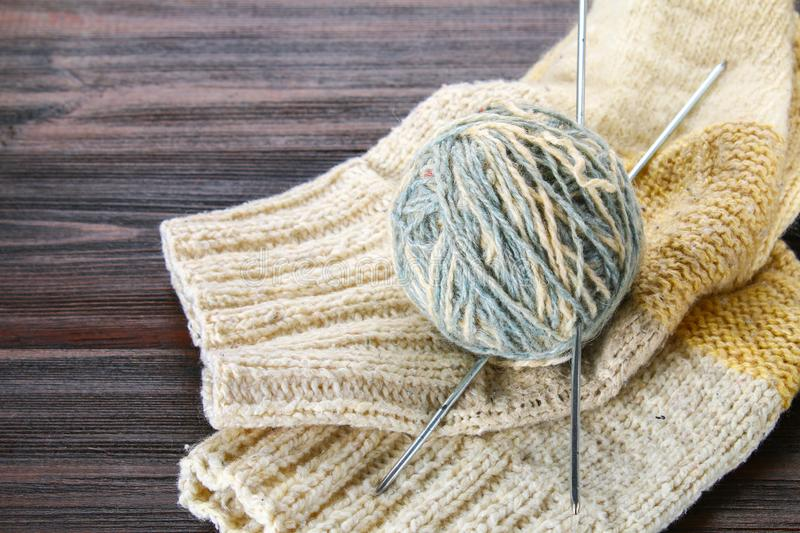 A ball of wool with knitting needles and knitted socks on a wooden table. Needlework. royalty free stock photos
