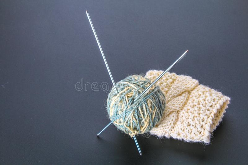 A ball of wool with knitting needles and socks on a gray table. Needlework. A ball of wool with knitting needles and socks on a gray table. Needlework stock photos