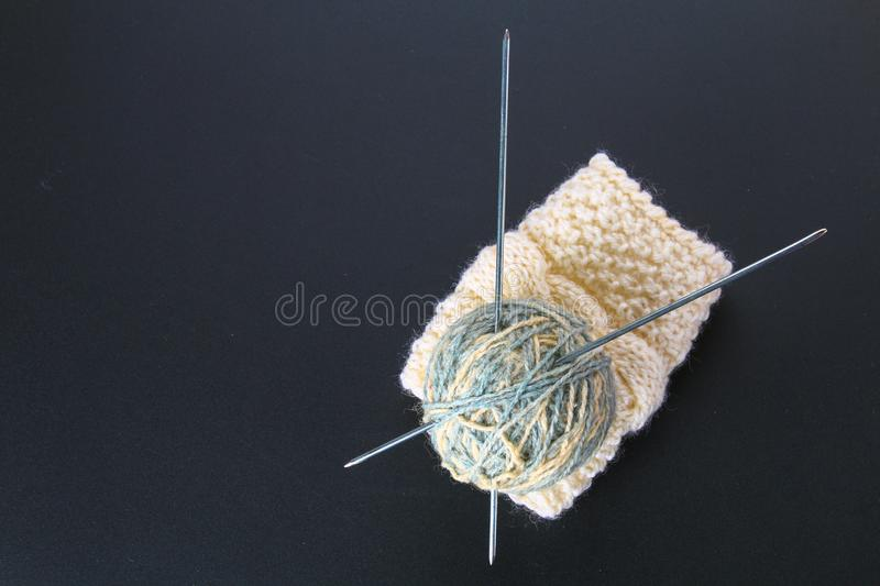 A ball of wool with knitting needles and socks on a gray table. Needlework. A ball of wool with knitting needles and socks on a gray table. Needlework stock photography