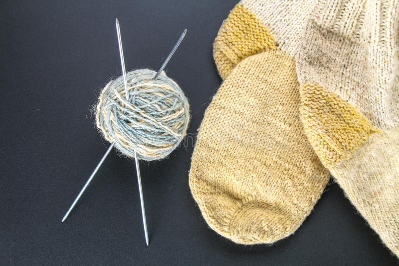 A ball of wool with knitting needles and socks on a gray table. Needlework. A ball of wool with knitting needles and socks on a gray table. Needlework stock image