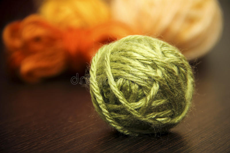 The ball of woolen threads. The ball of woolen threads on a dark background royalty free stock photo