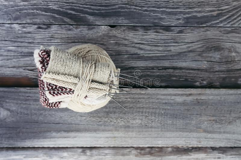 Ball of woolen yarn and knitting needles in a box on wooden boards background royalty free stock image