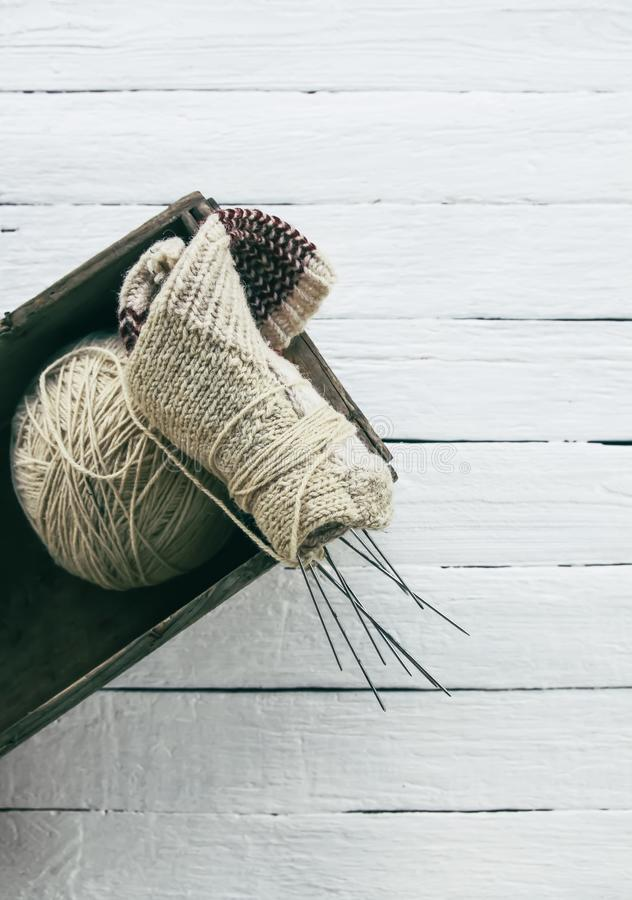Ball of woolen yarn and knitting needles in a box on wooden boards background stock images