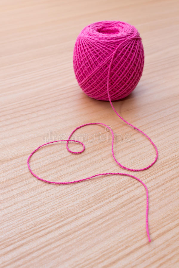 Ball of yarn and heart shape on a wooden table. Valentine's Day design stock photography