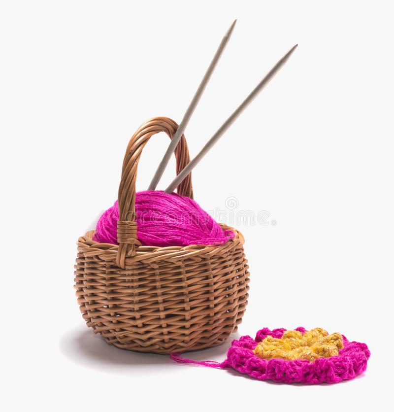 A ball of yarn with spokes in a basket on a white background stock image