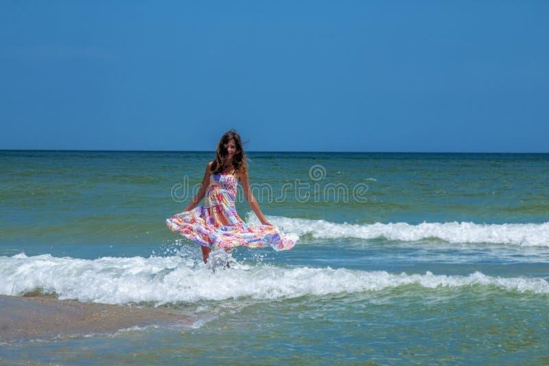 Ballando sull'acqua: ritratto di giovane bella donna in mare come simbolo di libert? e di felicit? Riflessione di luce solare in  fotografia stock