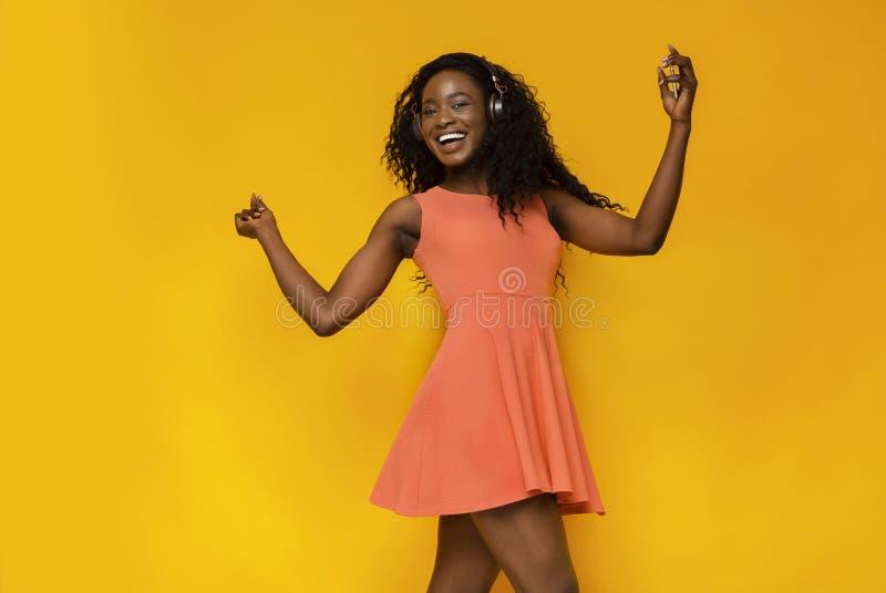 Ballare africano energetico della donna, ascoltante la musica favorita fotografie stock libere da diritti