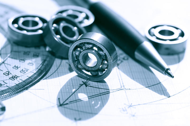 Ballbearings On Draft. Engineering concept. Few ball bearings near ruler and pen on graph paper background stock image
