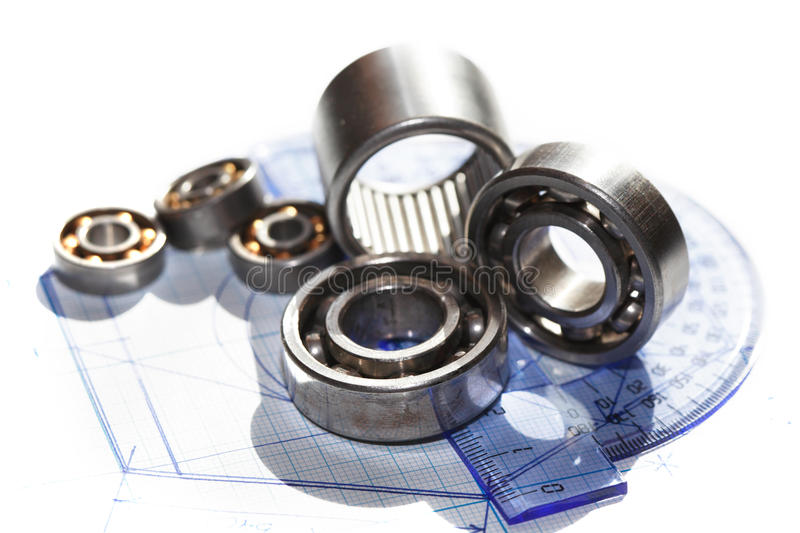 Ballbearings On Draft. Industrial concept. Few ballbearings near ruler on graph paper background royalty free stock photos