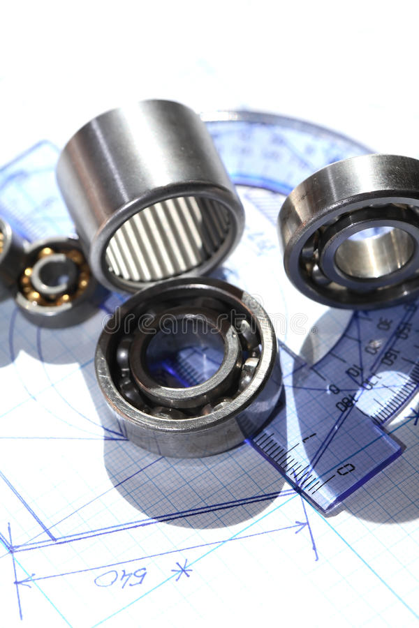 Ballbearings On Draft. Industrial concept. Few ballbearings near ruler on graph paper background stock images