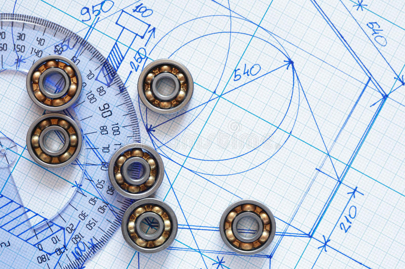 Ballbearings On Draft. Industrial concept. Few ballbearings near ruler on graph paper background royalty free stock images