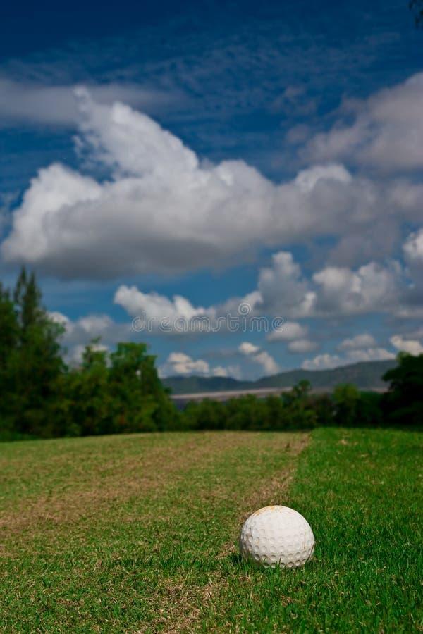 Balle de golf sur le cours et le ciel bleu photographie stock libre de droits