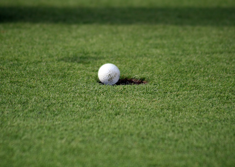 Balle de golf tombant dans le trou photo libre de droits