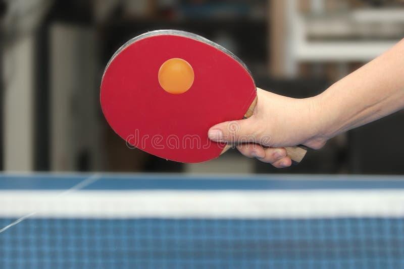 Balle de tennis orange tenue de table de counterhit d'avant-main près de filet sur le bl photographie stock libre de droits
