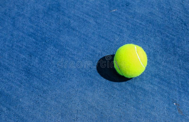 Balle de tennis sur la cour dure bleue photo stock