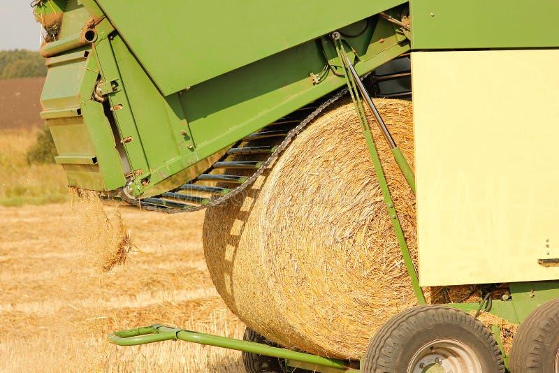 Balle di fieno in un campo con un trattore nei precedenti di autunno fotografie stock