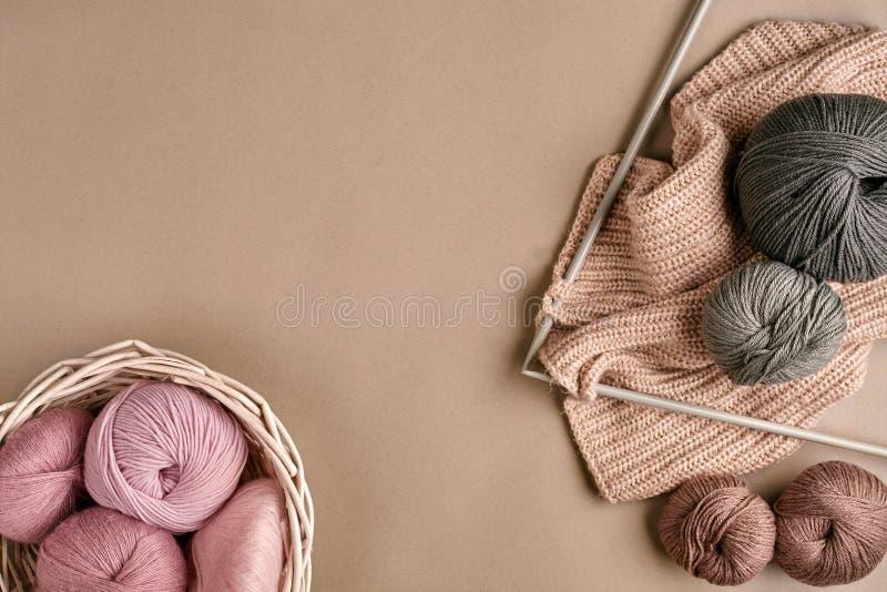 Ballen die van merinoswolgaren, op breinaalden op een beige oppervlakte breien Hoogste mening stock fotografie