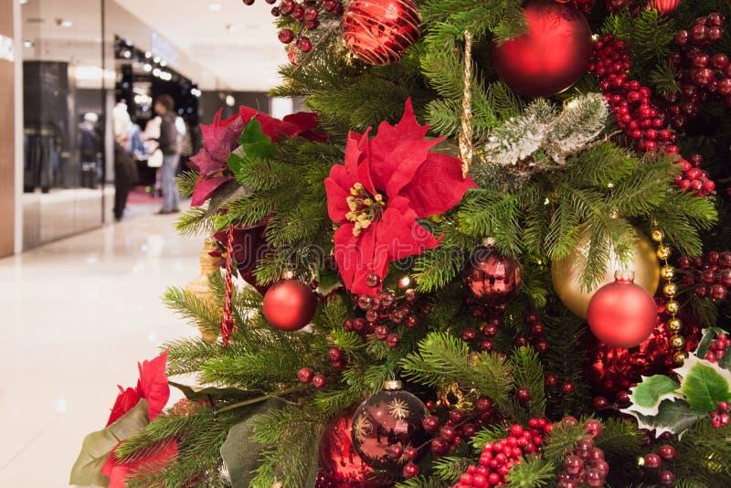 Ballen van de kerstboom de rode ontwerper op vage achtergrond in wandelgalerijbinnenland Kerstmispatroon Het winkelen en verkoop stock foto