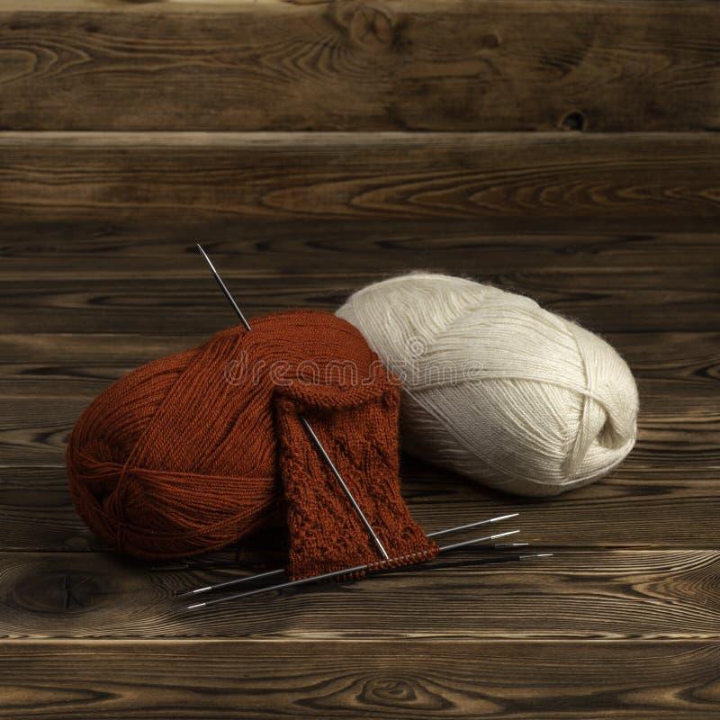 ballen van draad en breinaalden met het breien op een houten achtergrond royalty-vrije stock afbeelding