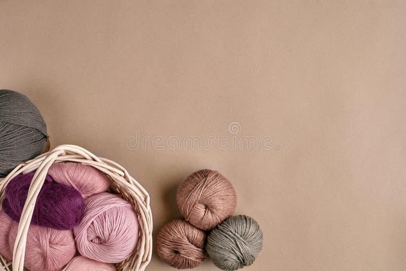 Ballen van garen en breinaalden Gekleurd garen voor het breien in een rieten kom op een beige achtergrond royalty-vrije stock foto