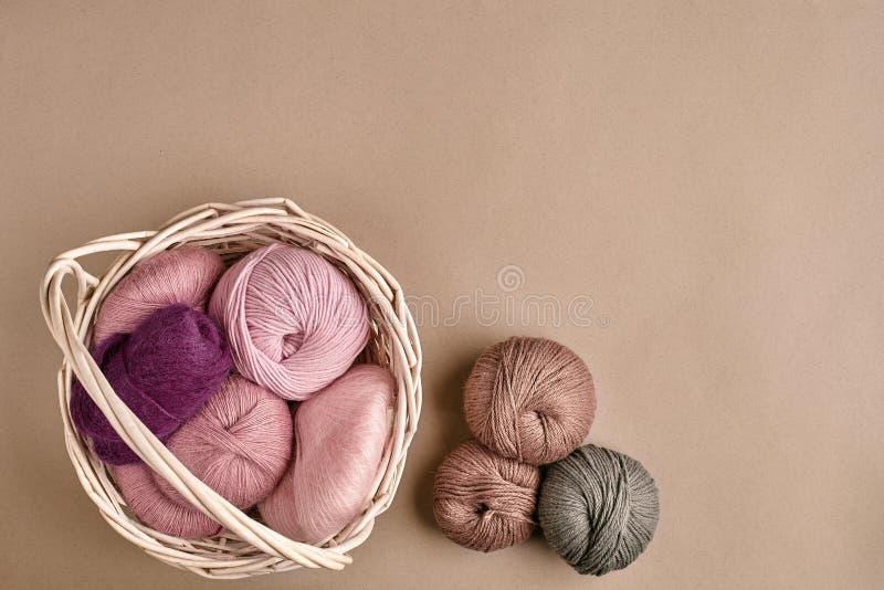 Ballen van garen en breinaalden Gekleurd garen voor het breien in een rieten kom op een beige achtergrond royalty-vrije stock afbeeldingen