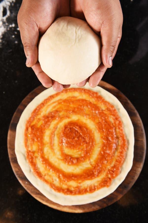 Ballen van vers pizzadeeg ter beschikking en tomatensaus op pizzabasis stock fotografie