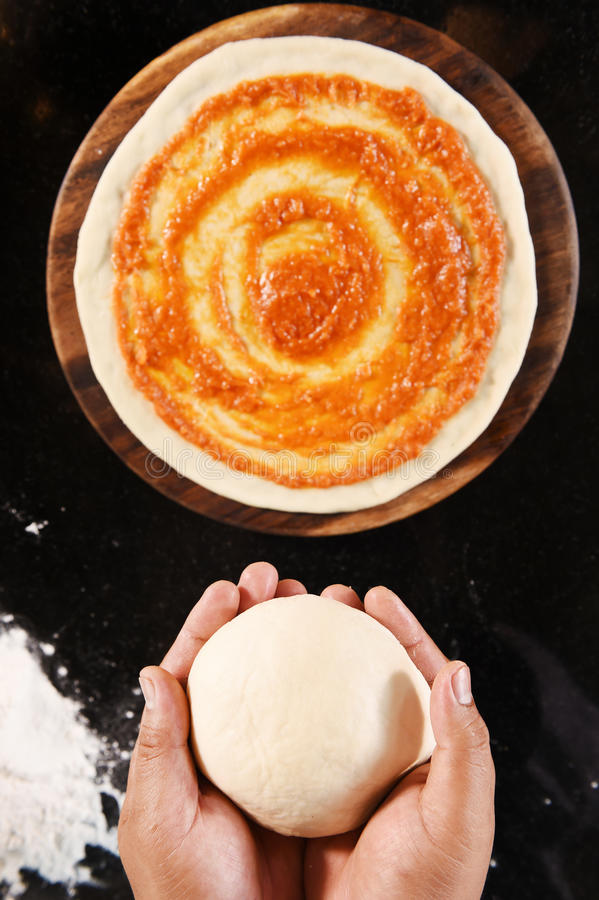 Ballen van vers pizzadeeg ter beschikking en tomatensaus op pizzabasis royalty-vrije stock foto's
