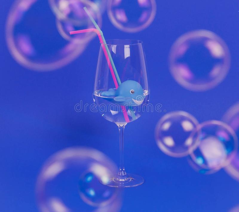 Ballena en vidrio con la paja del agua y del plástico Concepto ambiental fotografía de archivo libre de regalías