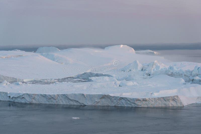 3 ballena jorobada bucear cerca de Ilulissat entre icebergs durante el sol rosa de medianoche Amanecer y atardecer Su fuente es l imagen de archivo libre de regalías