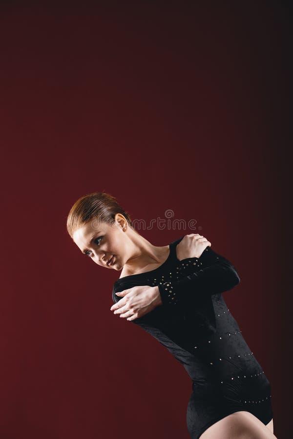 Ballerina που πραγματοποιεί τις ασκήσεις στο στούντιο στοκ φωτογραφία