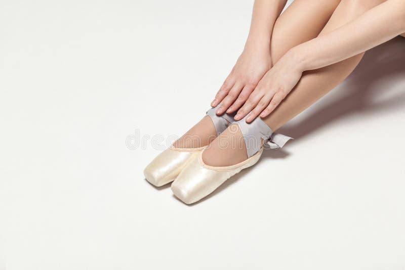 Ballerina στα παπούτσια pointe που κάθονται στο άσπρο πάτωμα, κινηματογράφηση σε πρώτο πλάνο στοκ εικόνες