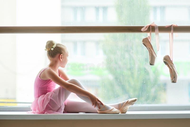 Ballerina στη ρόδινη συνεδρίαση φορεμάτων στην παράθυρο-στρωματοειδή φλέβα στοκ εικόνες