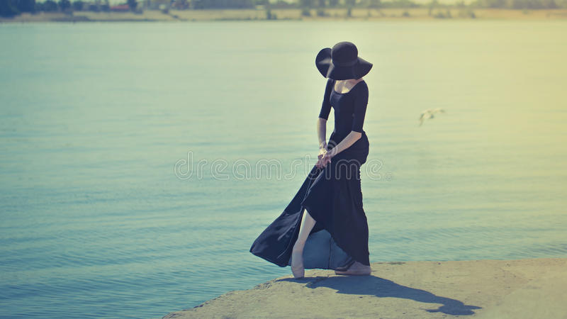 Ballerina στο καπέλο και το μαύρο φόρεμα που χορεύουν στο riverbank τονισμός στοκ εικόνα