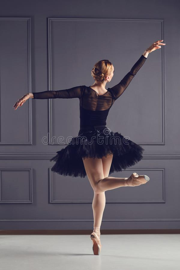 Ballerina dancer in black dress posing over gray background. Ballerina ballet dancer in black dress posing over gray background back view royalty free stock photography