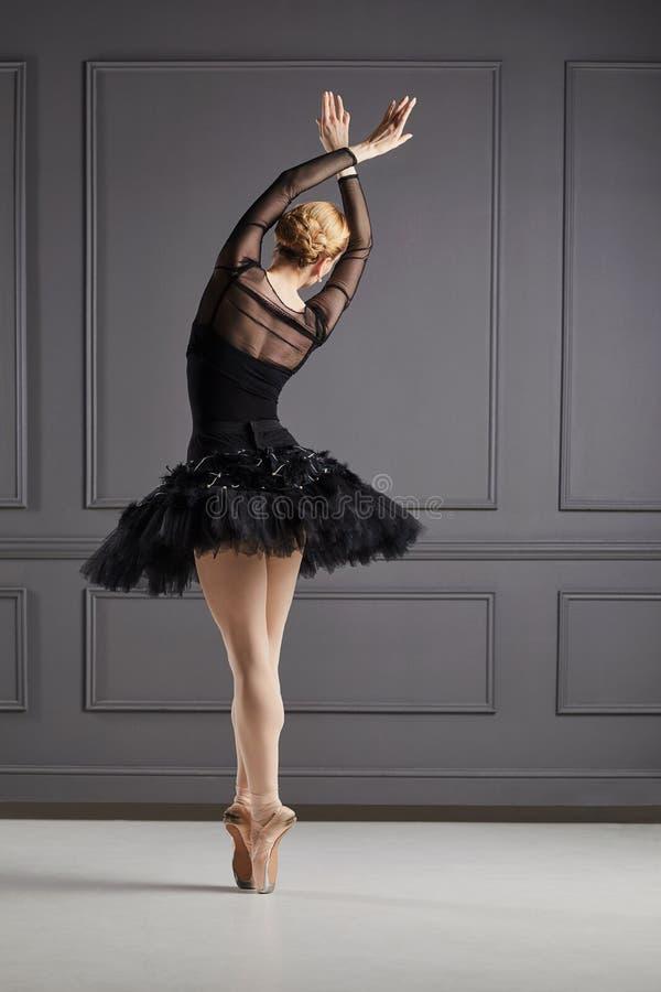 Ballerina ballet dancer over gray background. Ballerina ballet dancer in black dress posing over gray background back view stock photo
