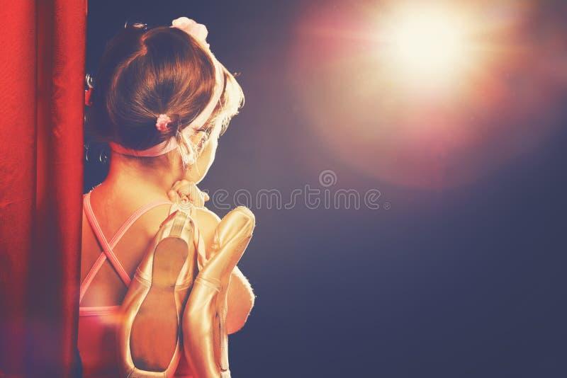 Ballerina-Balletttänzer des kleinen Mädchens auf Stadium in den roten Seitenszenen stockfotos
