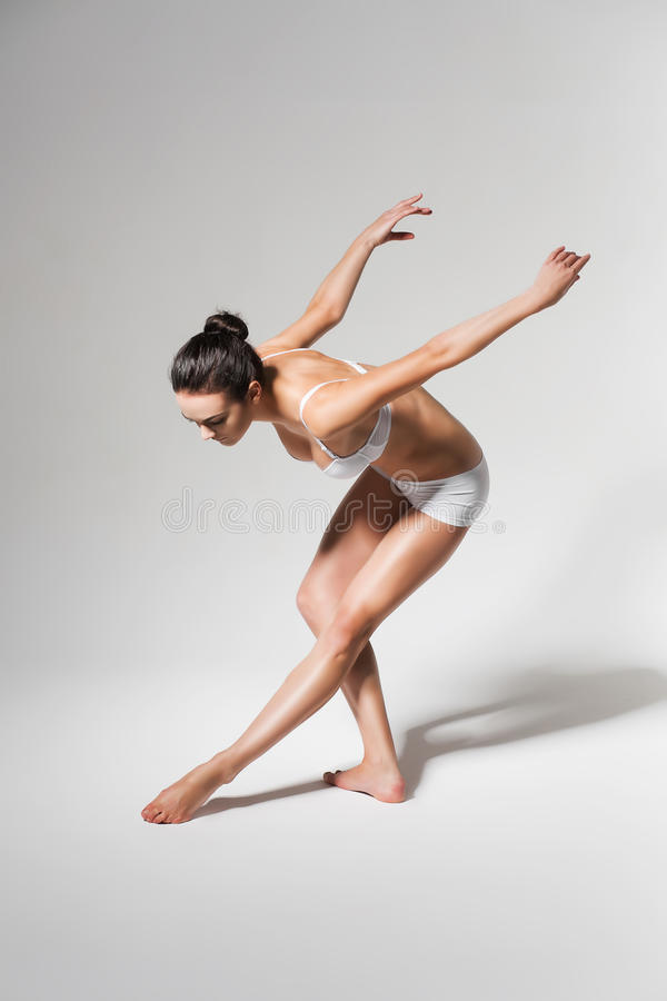 Ballerina bending down to leg stock photo