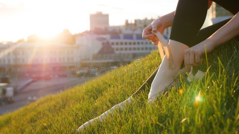 Ballerina bindet oben ihre pointe Schuhe, die auf dem grünen Gras auf dem Hügel sitzen lizenzfreie stockfotografie