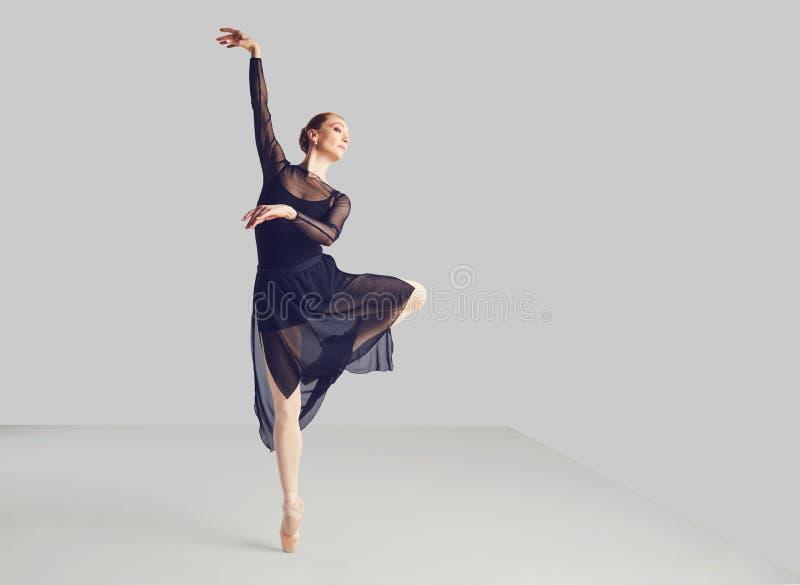 Ballerina in a black tutu elegantly dancing on a black background. Concept ballet dancing dancer stock photos