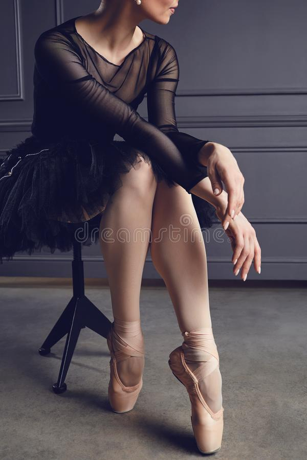 Ballerina in a black tutu sits on a chair on a black background. Concept ballet dancing dancer stock photo