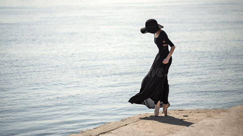 Ballerina in cappello e vestito nero fotografia stock libera da diritti