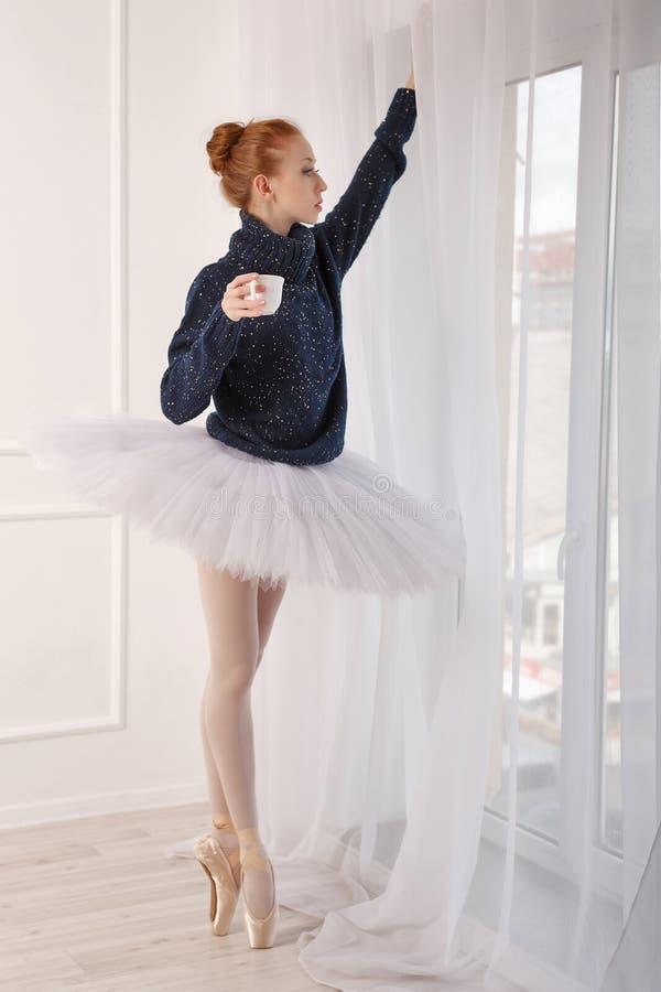 Ballerina che beve tè nero dalla finestra fotografie stock libere da diritti