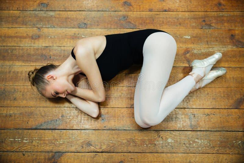 Ballerina che dorme sul pavimento di legno immagini stock
