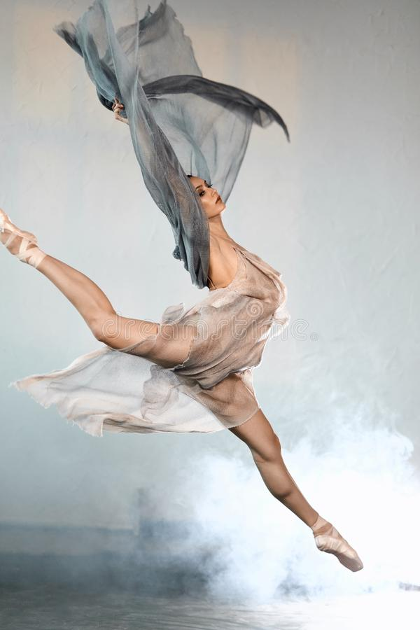 Ballerina che indossa i vestiti trasparenti grigi che saltano in scena con l'effetto del fumo fotografie stock