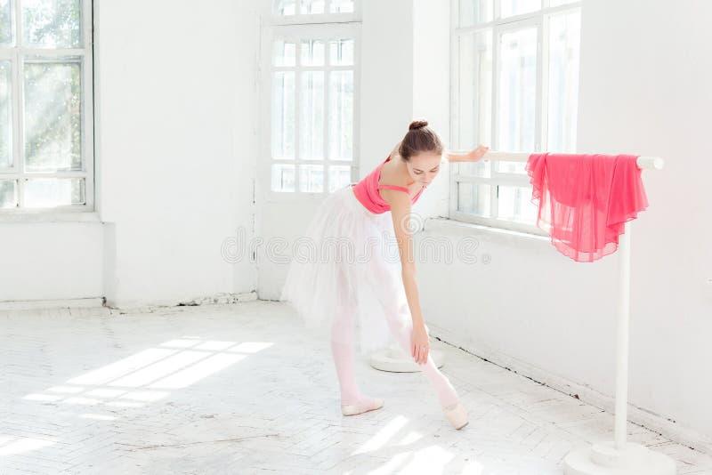 Ballerina che posa in scarpe del pointe al padiglione di legno bianco fotografia stock libera da diritti
