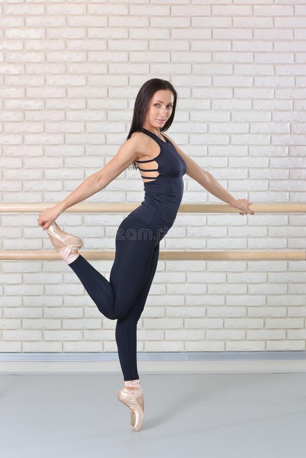 Ballerina che posa vicino alla sbarra allo studio di balletto, ritratto integrale di bello ballerino della donna che esamina macc immagini stock libere da diritti