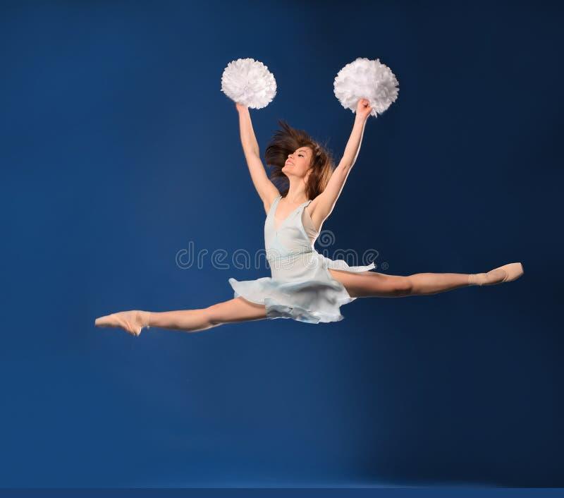 Ballerina cheerleader. Jumping with hands raised stock image