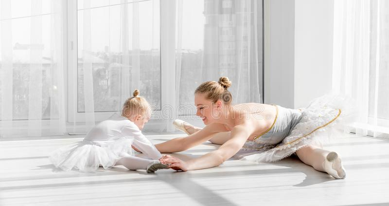 Ballerina with child girl warming up before training royalty free stock photo
